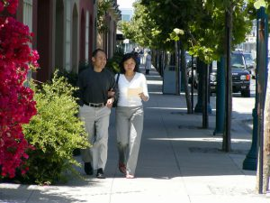 Two people walking on a sidewalk in San Francisco.